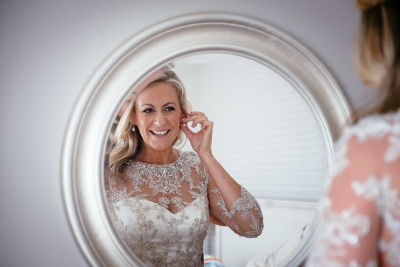 bride getting ready on her wedding morning in front of a mirror
