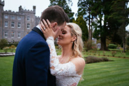 bride and groom kissing in front of an irish castle