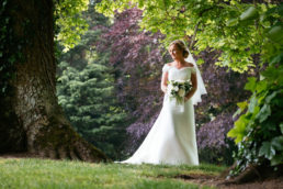 bride standing by a tree in the grounds of dunboyne castle hotel on her wedding day