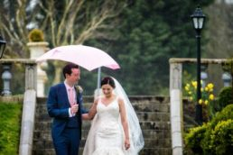 bride and groom walking through rain with groom holding a white umbrella