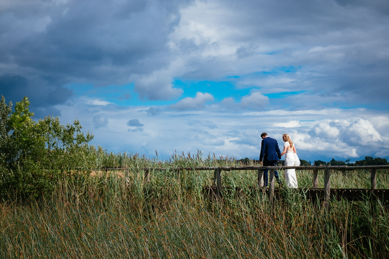 bride and groom walking on a bridge at glasson house athlone