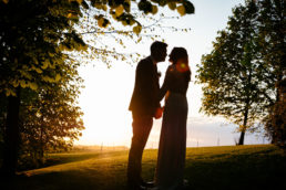 bride and groom kissing with the sun setting behind them at their kilshane house wedding in tipperary ireland