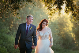bride and groom walking through forest at sunset during their cabra castle wedding