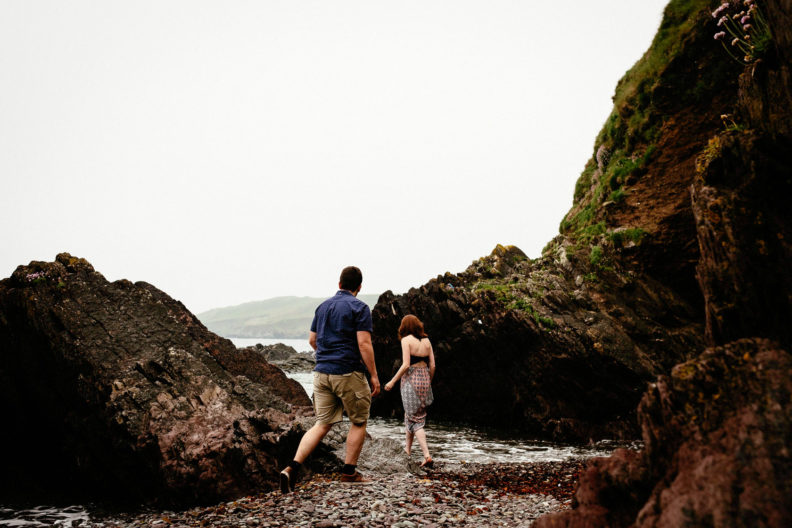 engaged couple walking along a beach in ballycotton county cork ireland