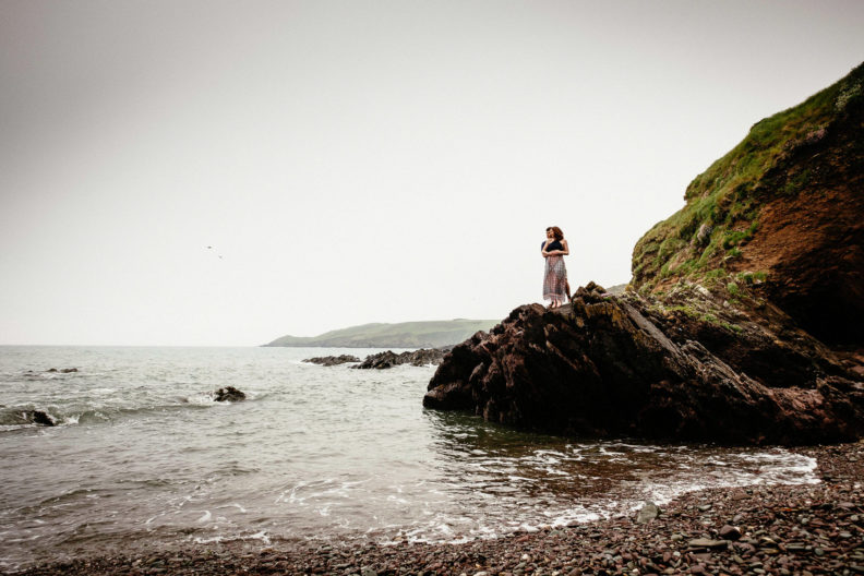 engaged couple embracing on a cliff in ballycotton county cork ireland