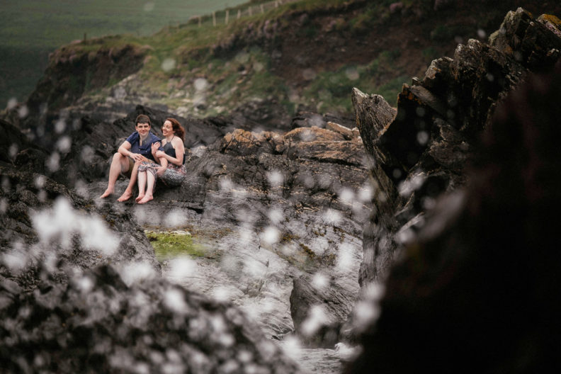 engaged couple sitting on rocks on a beach in ballycotton county cork ireland
