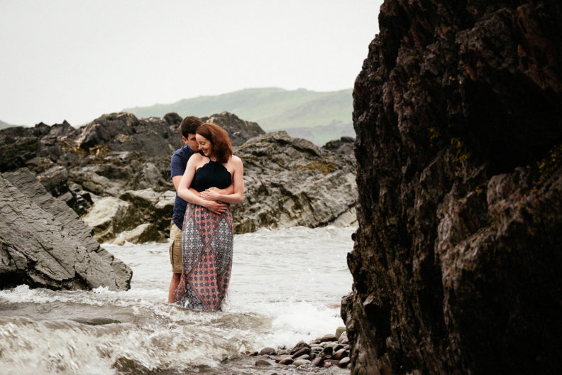 engaged couple standing in the sea off the coast of county cork ireland