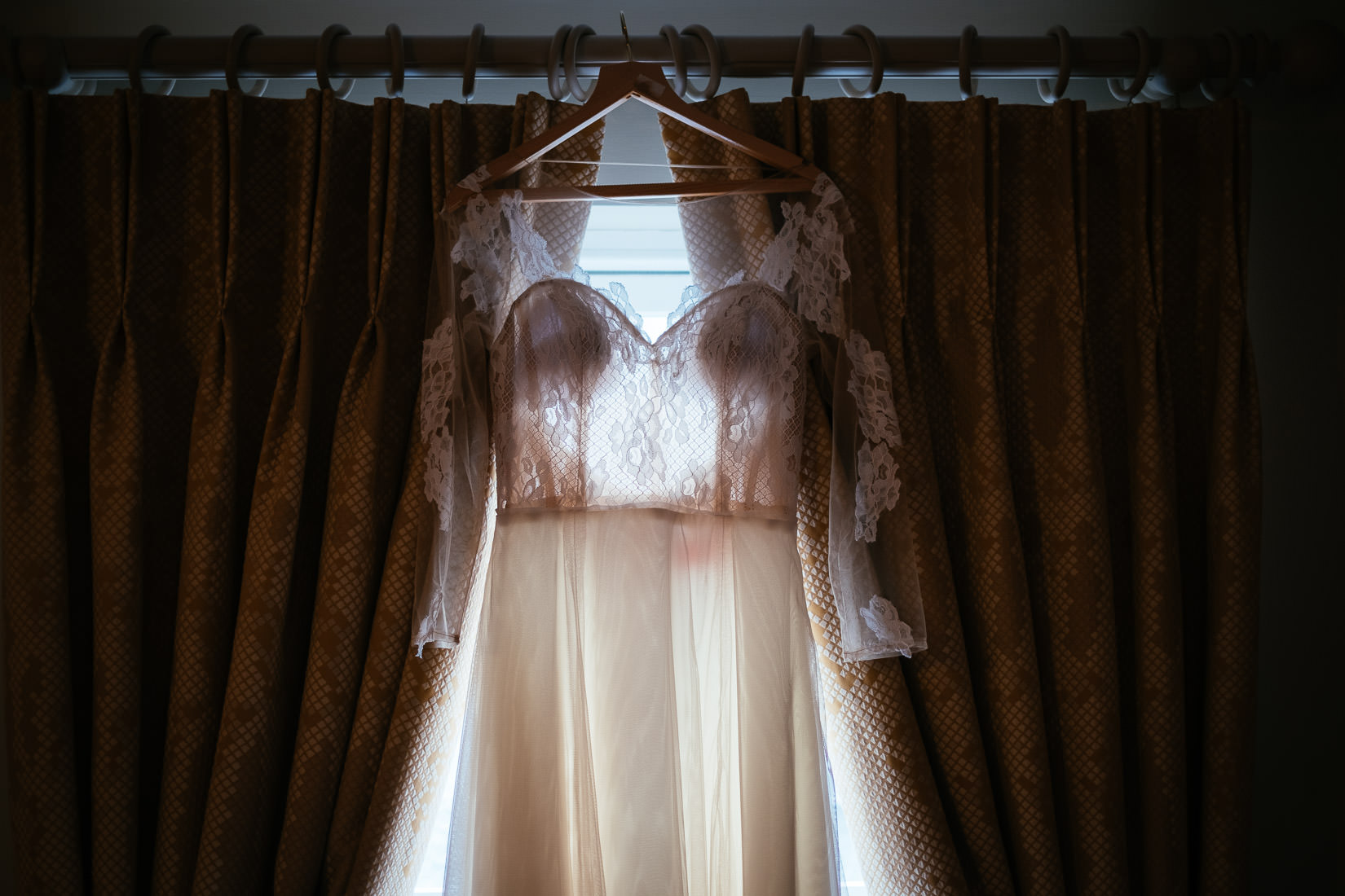 wedding dress hanging in a window