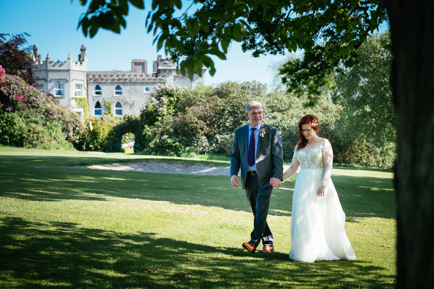 bride and groom walking through the grounds at cabra castle