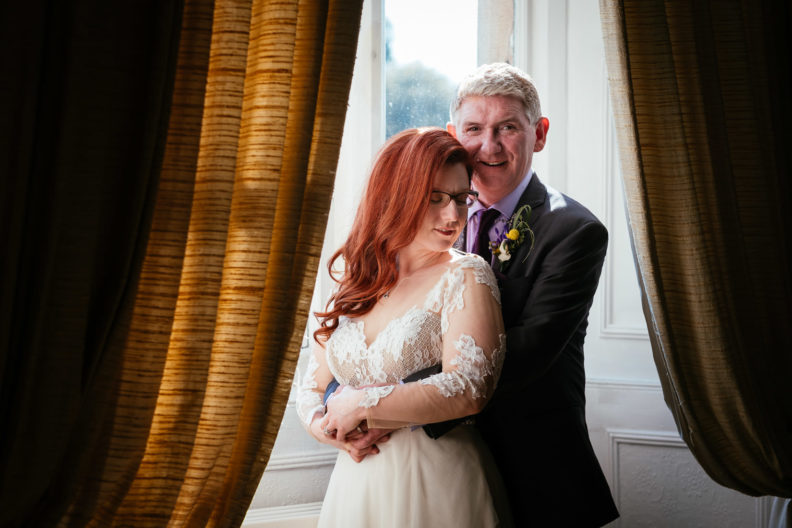 bride and groom hugging at a window at cabra castle