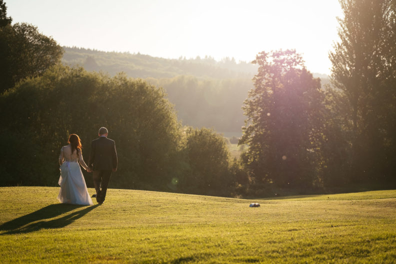 bride and groom walking into the sunset at cabra castle
