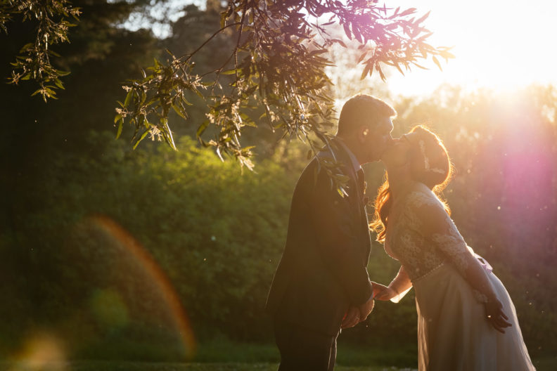 bride and groom kissing under a tree at cabra castle at sunset