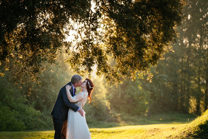 bride and groom kissing under a tree at cabra castle as the sun sets behind them