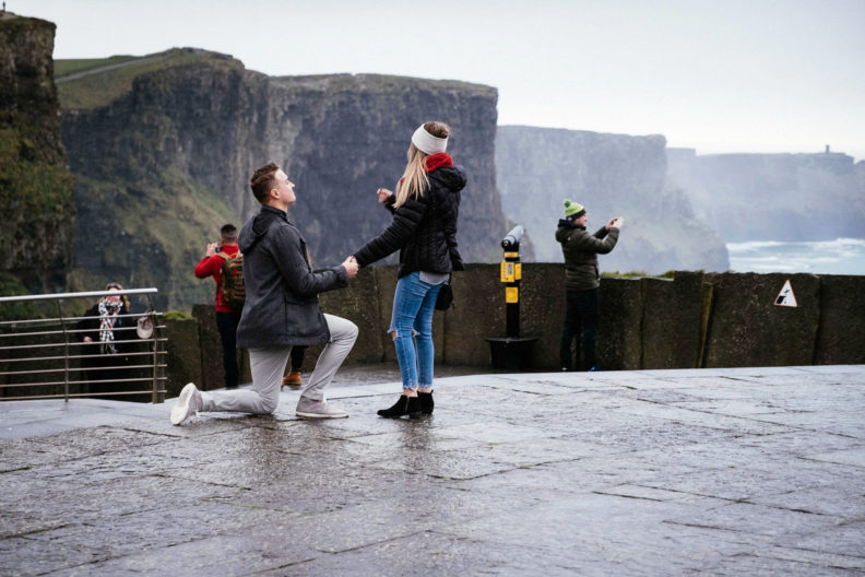 guy on one knee proposing at the cliffs of moher