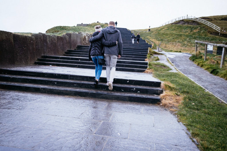newly engaged couple walking up steps at the cliffs of moher