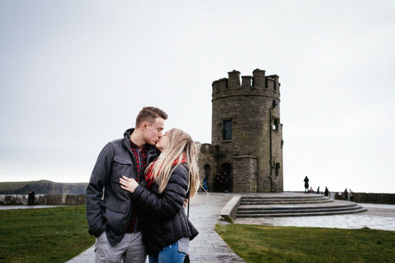 ewly engaged couple kissing at the cliffs of moher