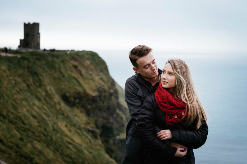 newly engaged couple embracing at the cliffs of moher