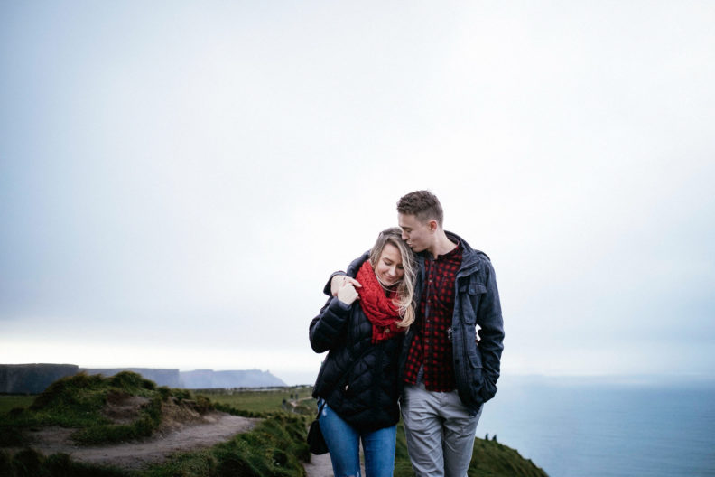 newly engaged couple walking along path at the cliffs of moher