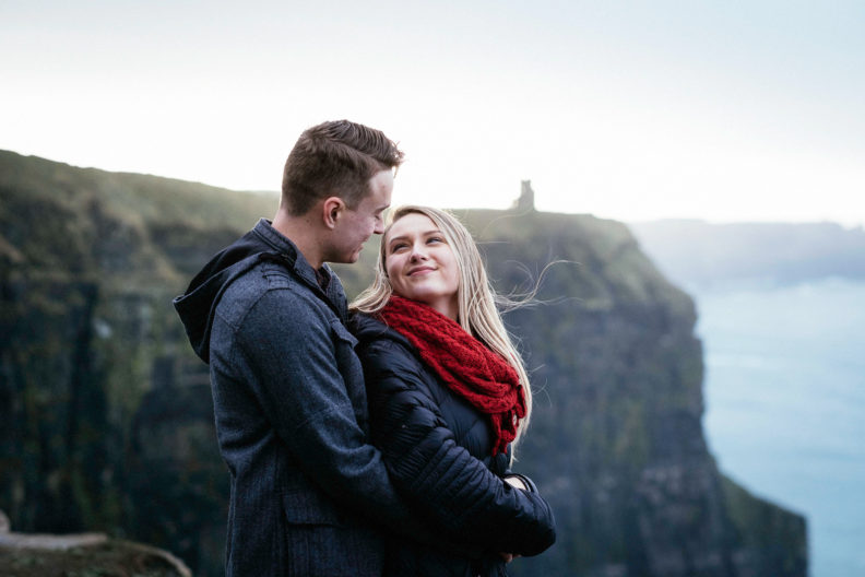 newly engaged couple embracing at the cliffs of moher with tower in background