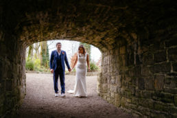 bride and groom walking under an arch holding hands