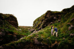 newly engaged couple climbing a cliff in ballycotton cork ireland