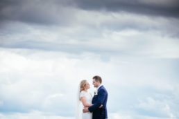 bride and groom facing each other against a cloudy sky
