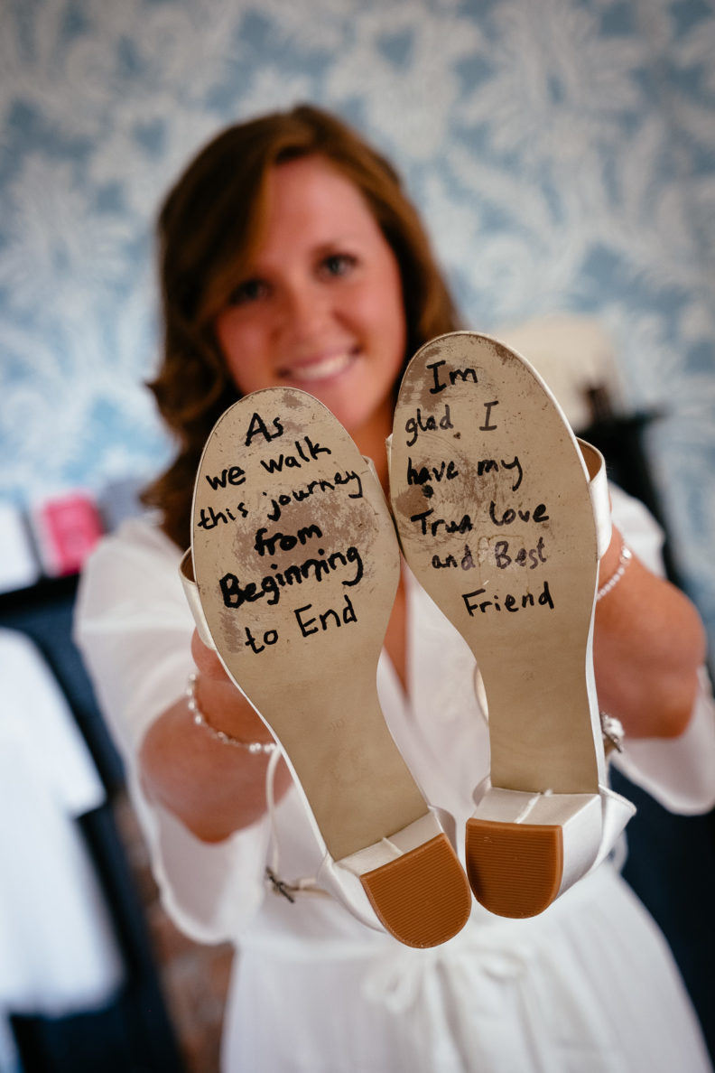 bride holding her wedding shoes