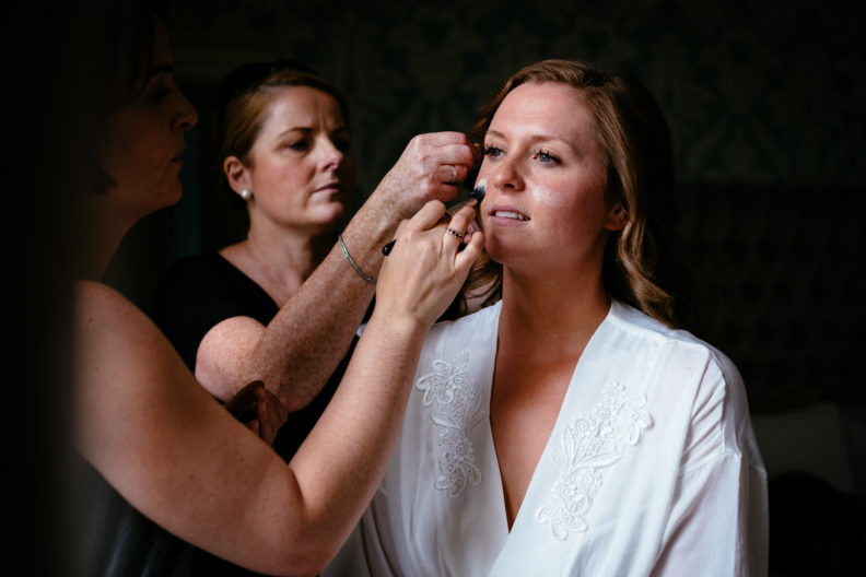 bride getting makeup applied to her face