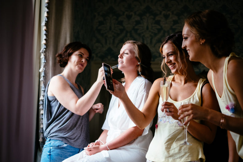 bride getting makeup alliped whilst bridesmaids laugh