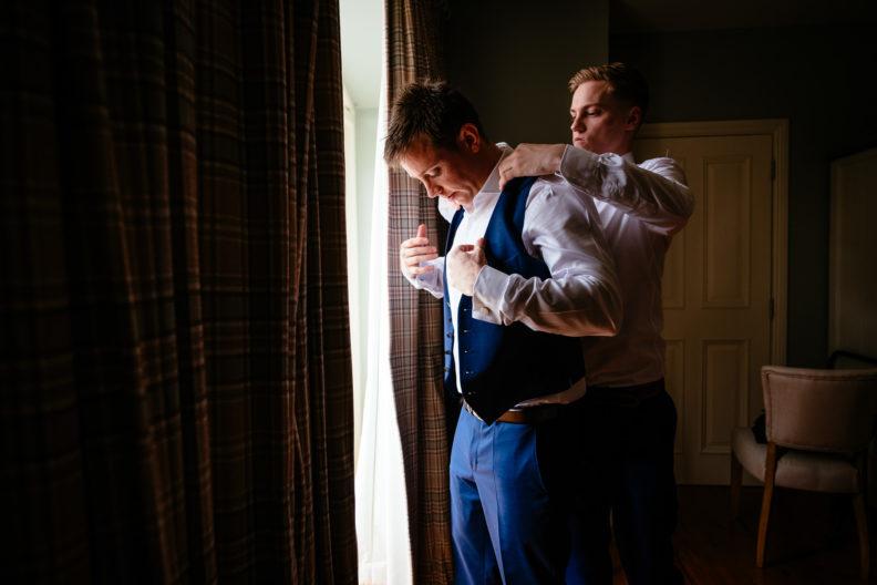groom putting his waistcoat on