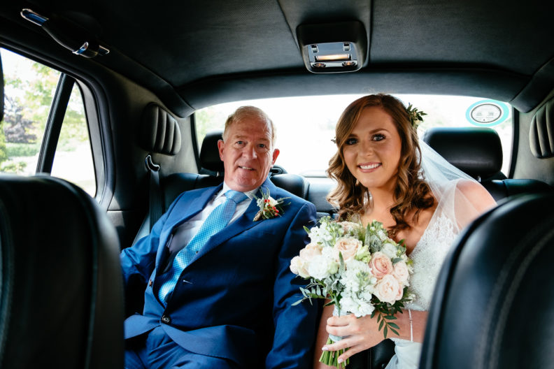 bride sitting in a car with her father