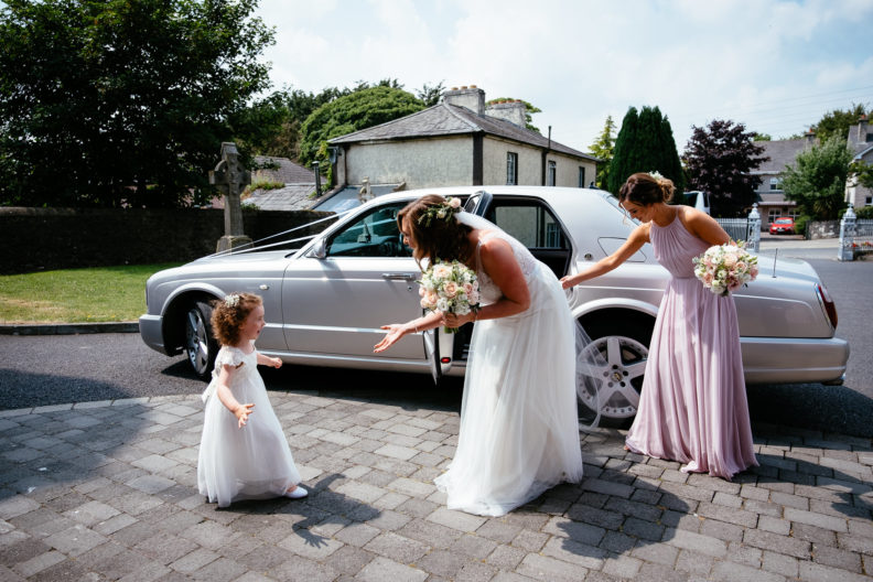 bride with flower girl outside church