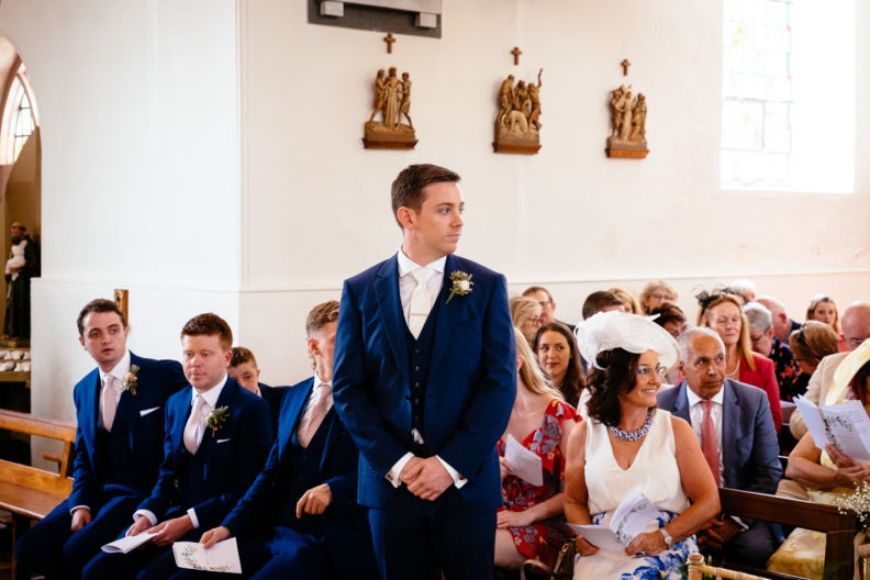 groom waiting for bride at top of alter