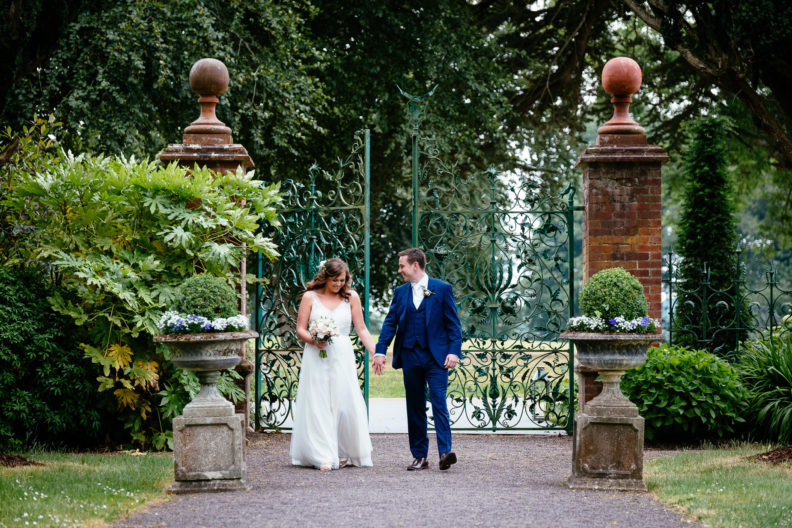 bride and groom walking in a walled garden