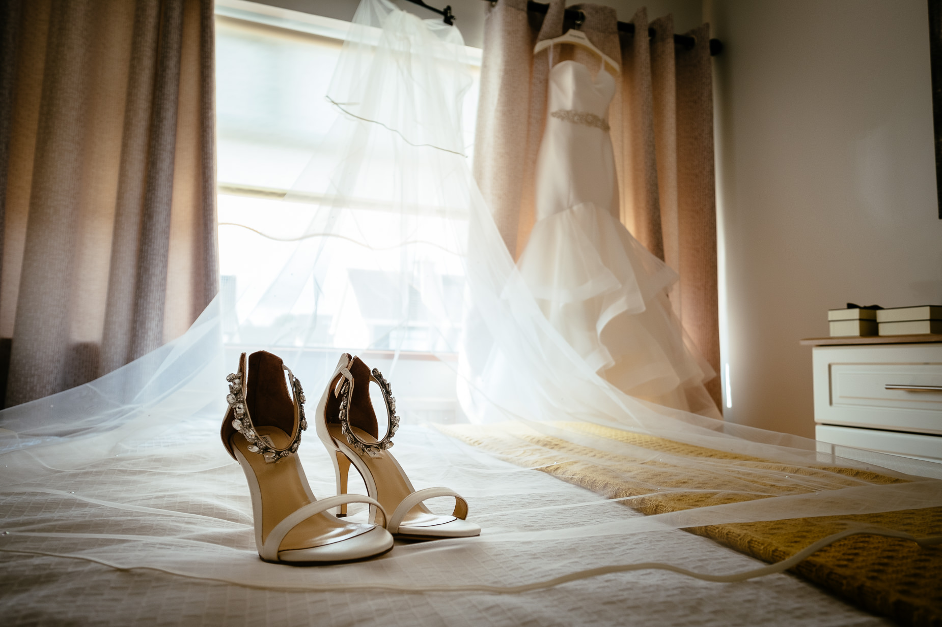 brides shoes sitting on bed