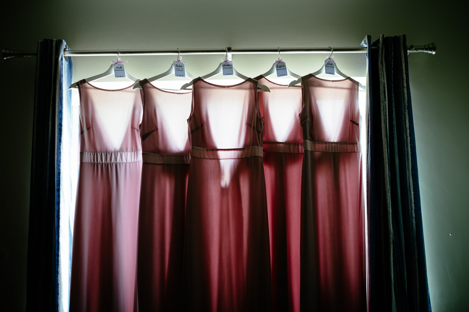 bridesmaids dress hanging by a window