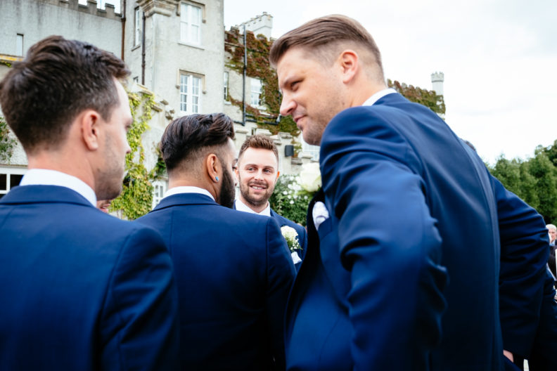groom laughing with groomsmen at Castle Bellingham