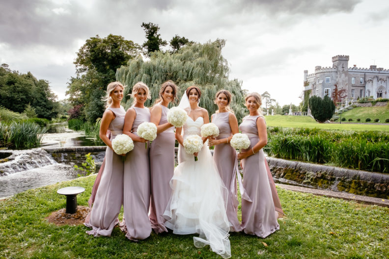 bridesmaids standing in front of weir and castle