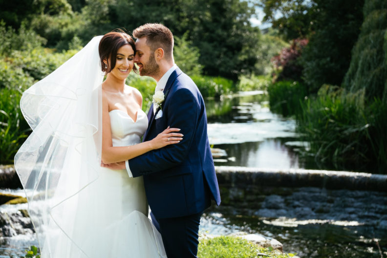 bride and groom embracing in front of a river