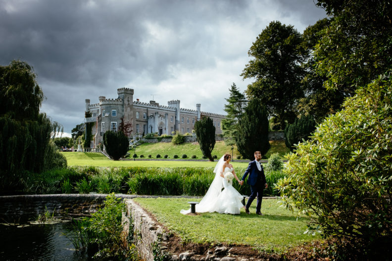 bride and groom with castle in background