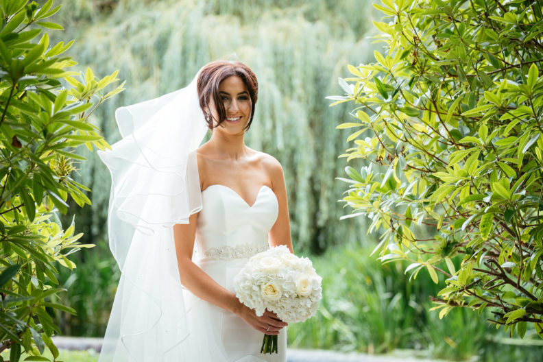 bride standing in front of a river