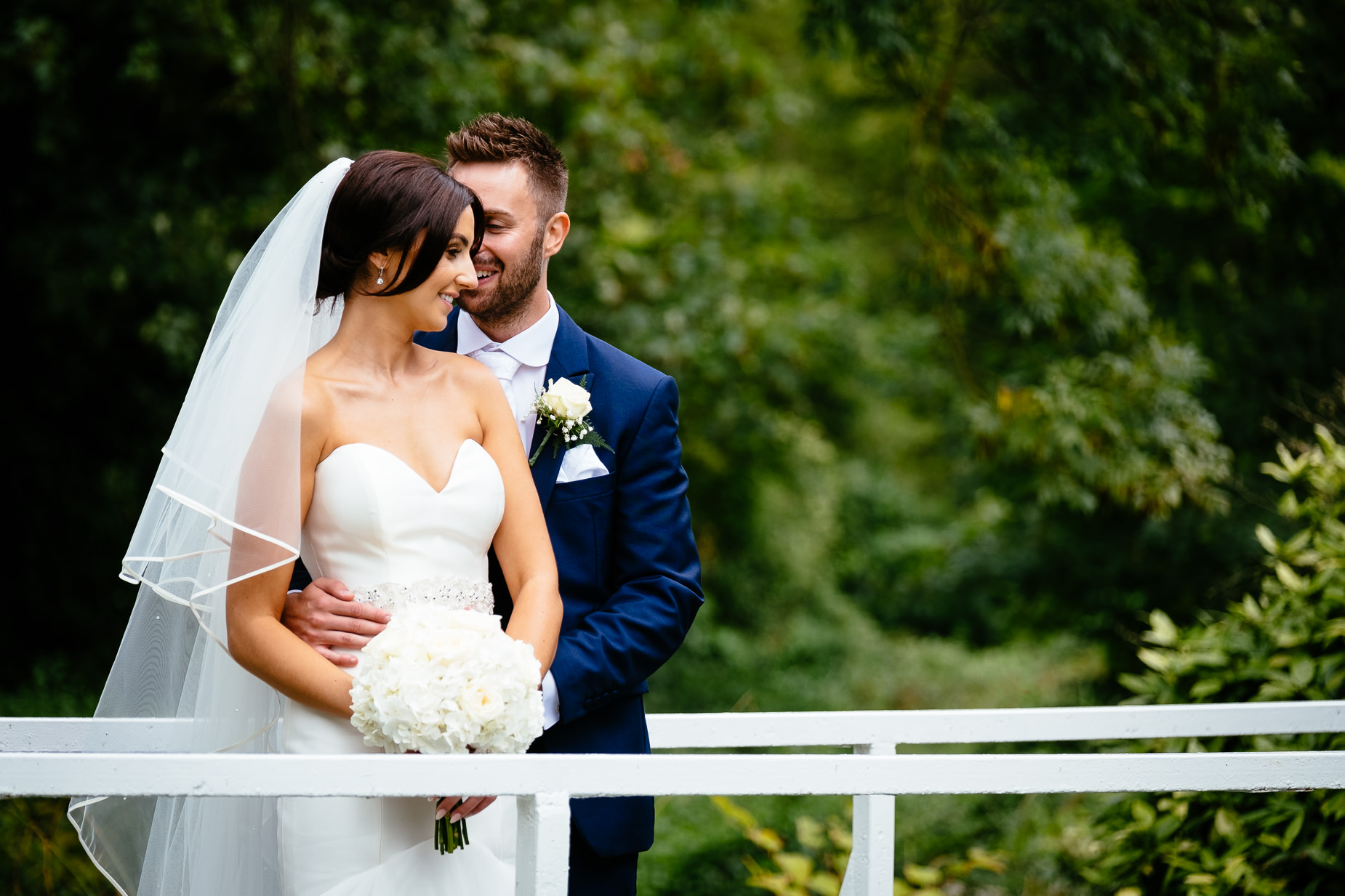 bride and groom embracing on a bridge