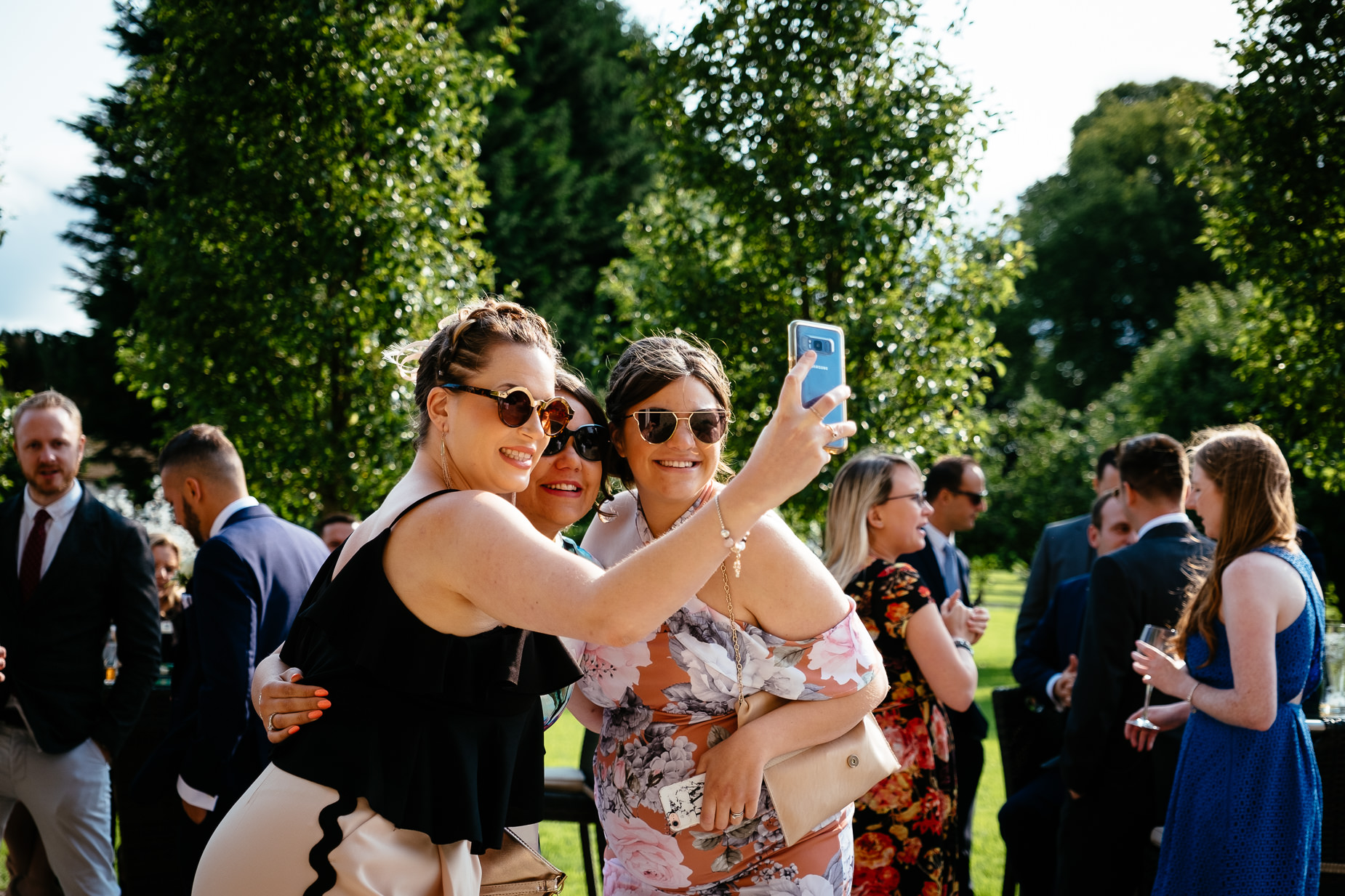 three wedding guests taking a selfie