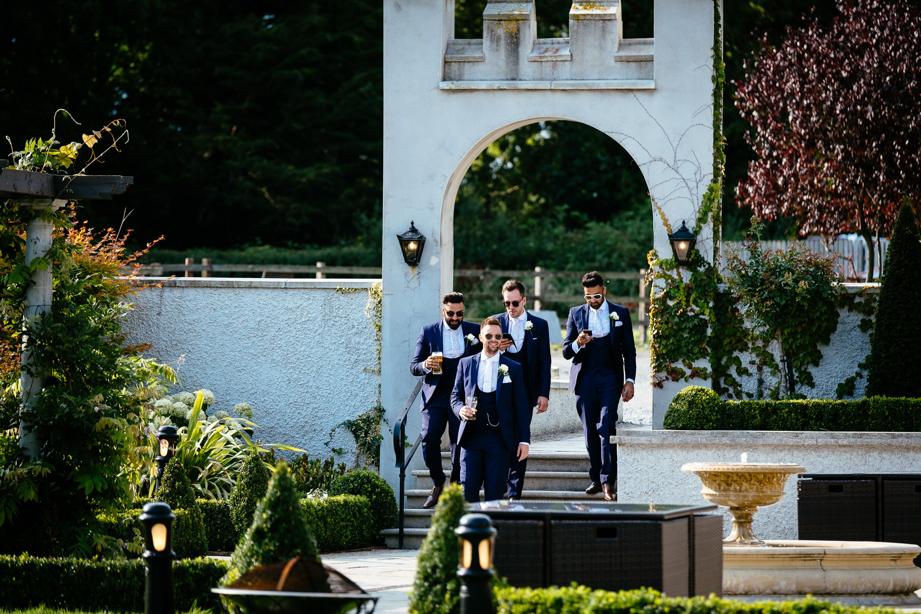 groomsmen walking through courtyard towards camera carrying drinks