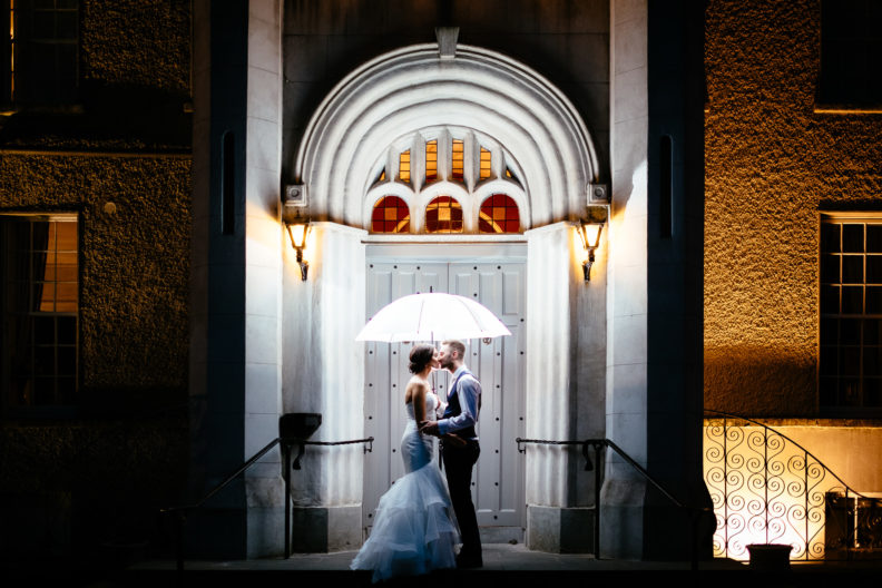 bride and groom standing outside main door of castle bellingham at night