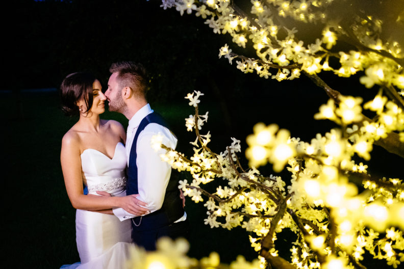 bride and groom kissing beside lit up tree at night