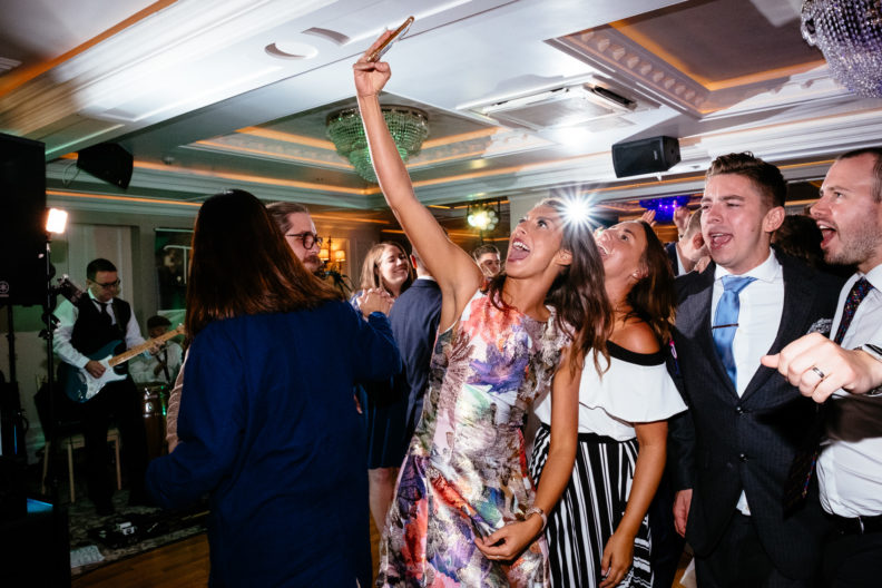 wedding guest taking a selfie of herself on dance floor