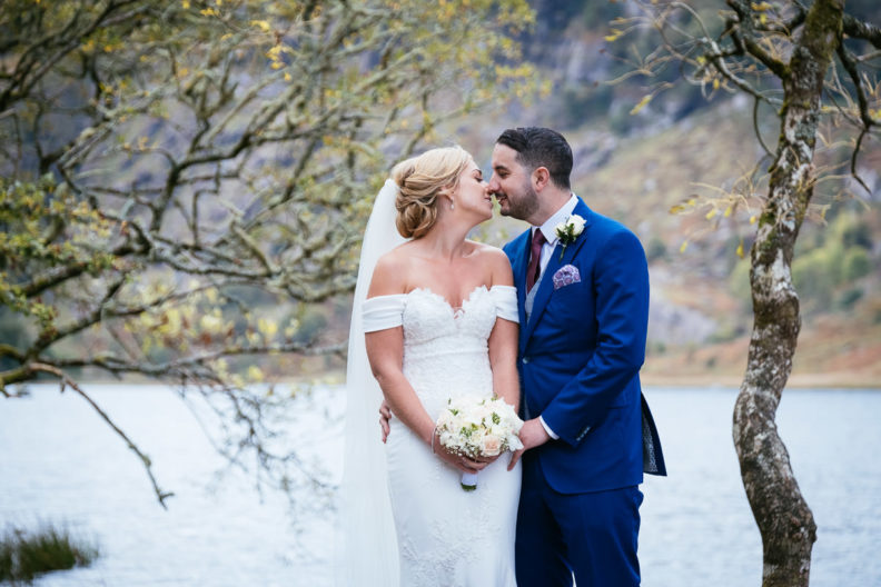 bride and groom kissinbg with a lake in the background at Gougane Barra