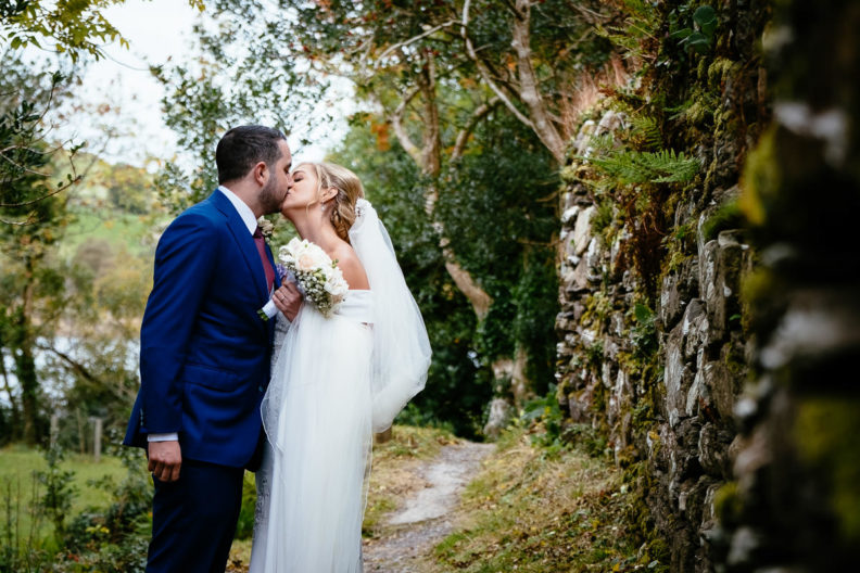 bride and groom kissing by a stone wall at Gougane Barra