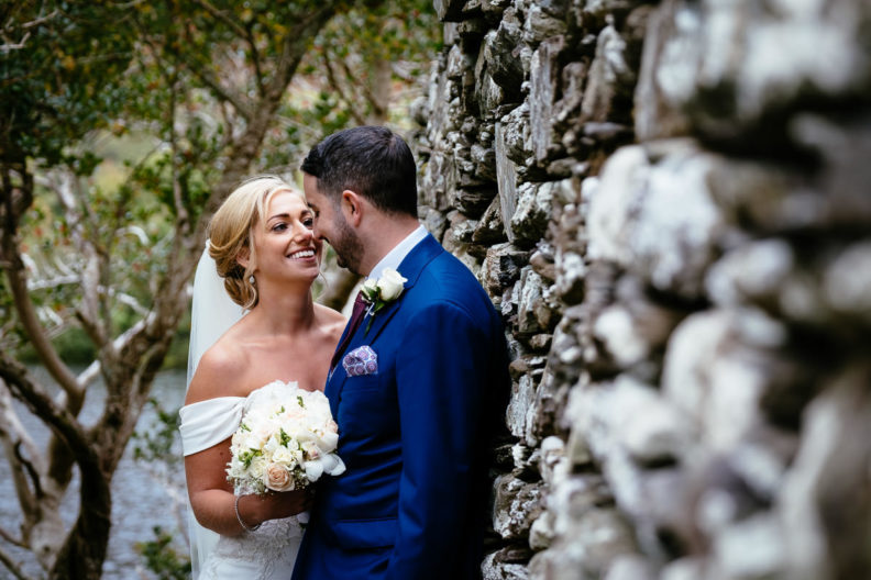 bride and groom embracing by a stone wall at Gougane Barra